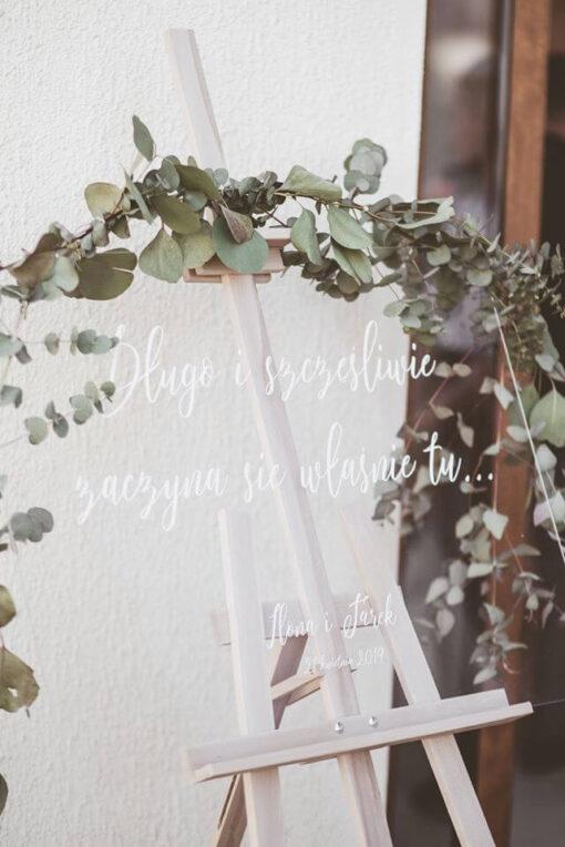 Ślubna, przezroczysta, tablica powitalna przyozdobiona eukaliptusem